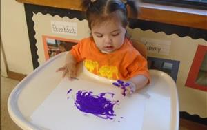 Our infants exploring their senses through finger painting.