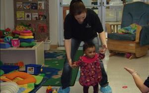 Our infants learning to walk with the support of the teachers.