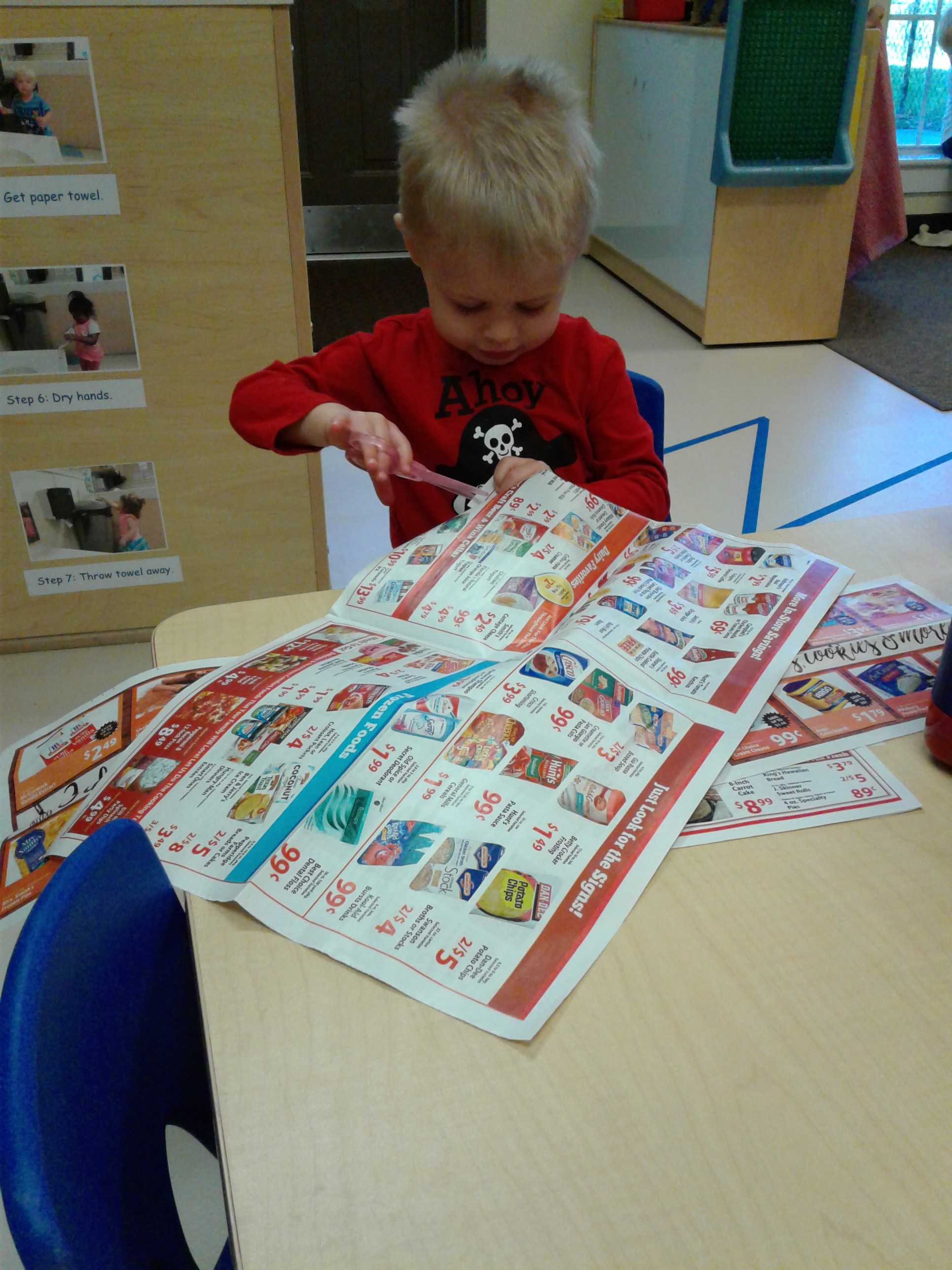 Our Toddler classroom was learning about Foods and Flavors. This child was practicing his fine-motor skills by cutting out food ads from a magazine. We always like to have materials in the classroom that the children would see in their real environment.