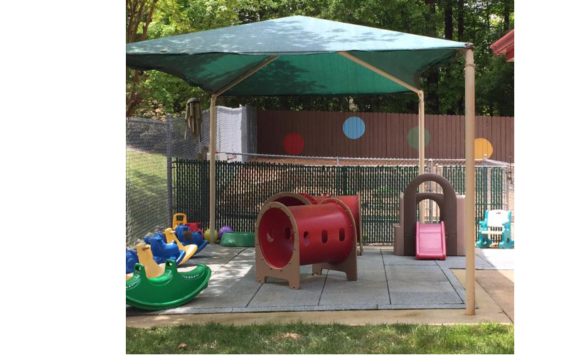 Our Toddler playground offers grassy areas to allow sensory and nature exploration. It also offers a padded and covered area with slides and tunnels to promote gross motor and social skills. A variety of pushing toys allows children who are beginning to walk or are just starting to walk to build strong muscles!