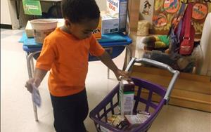 Children engaging in dramatic play (grocery store) in the Preschool class.