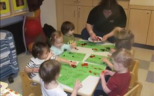 Our Toddlers creating ladybug art collages using their fine motor skills to glue felt on to their bugs