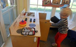 We like to make our themes come to life. The dramatic play area has been transformed into a house. This child is pretending to bake, so she made sure to wear her oven mitt to take something out of the hot oven!