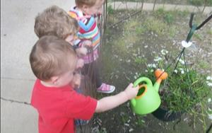 Toddlers watering their garden on the playground.