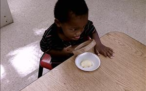 One of our preschool students uses a magnifying glass to examine his apple slices before sampling.