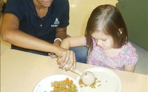 Family style dining is an important component of our program.  Ms. Angel is helping Isla serve her own food during lunch time.
