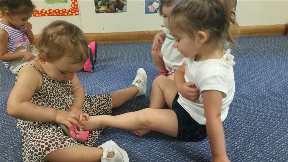 In our center, our children learn to help their friends at infancy.  Here Riley is helping Sophia put her shoe back on in the toddler room.