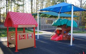 Infant/Toddler Playground features an open climb through tree and a covered picnic clubhouse with table and benches. This playground also has a rubber play surface and a tricycle track.