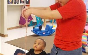 Ms. Rosa helps our toddlers explore their senses as they feel and smell the goop they made!