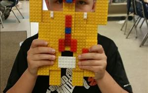 A student is exploring and building with Legos in our School Age Classroom.