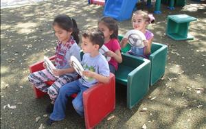 VPK students pretending to drive a bus on the playground for their transportation unit.