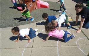 Our Discovery Preschool Classroom is showing us their physical development and wellness by working on moving like animals outside with Ms. Ashley.