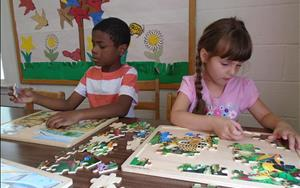 Pre Kindergarteners learn logic and problem-solving skills through working puzzles.