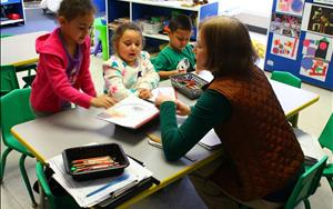Ms. Judith assists her Prekindergarteners as they complete their journals!