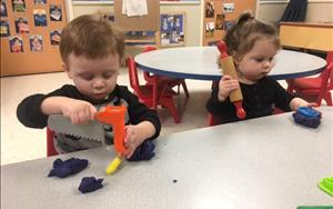 Toddlers using their fine motor skills with playdough.