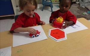 Anika is exploring painting with using vehicle wheels instead of a paint brush.