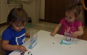 Toddlers use creative materials to create sensory bags.
