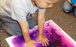 In this photo we have a child showing us how our gel tiles can help soothe someone when they are overwhelmed, sad, over stimulated and even bored with other activities. These awesome gel tiles are in each one of our classrooms and available to all of the children when needed. They are an integral part of our postitive behavior plan.