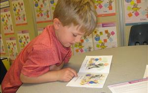 One of our children reading a book during our Vowels and Blending Learning Adventures class.