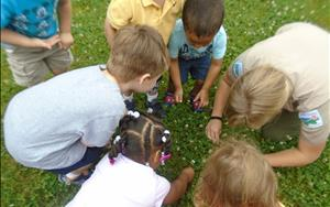 Preschool and Pre K Students with a Naturalist learning about what is in the ground.