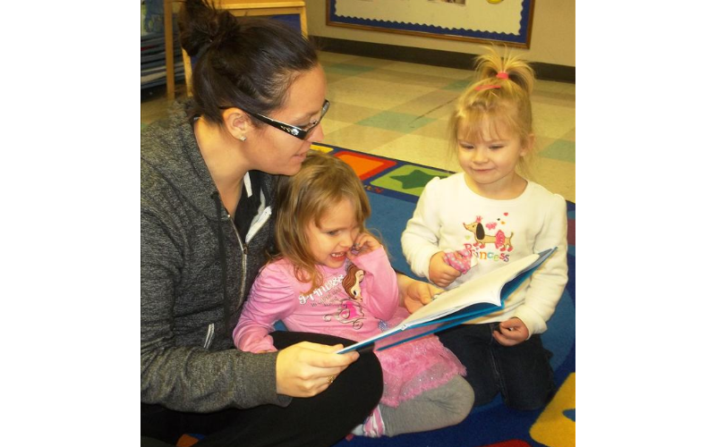 The children love going into the library center and reading stories with Ms. Elizabeth!