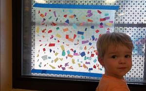 One of our Toddlers adding paper to our giant suncatcher.