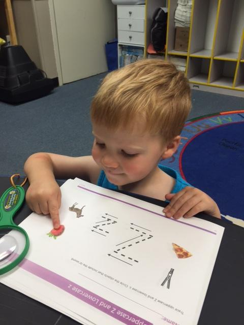 Gavin is working hard to sound out his phonics small group activity.