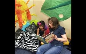 One of our Two year old's reading with Ms. Tina!