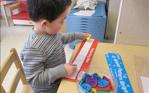 Christopher is learning math by making patterns in PreK.