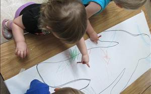 Toddlers hard at work drawing and learning about the human body.
