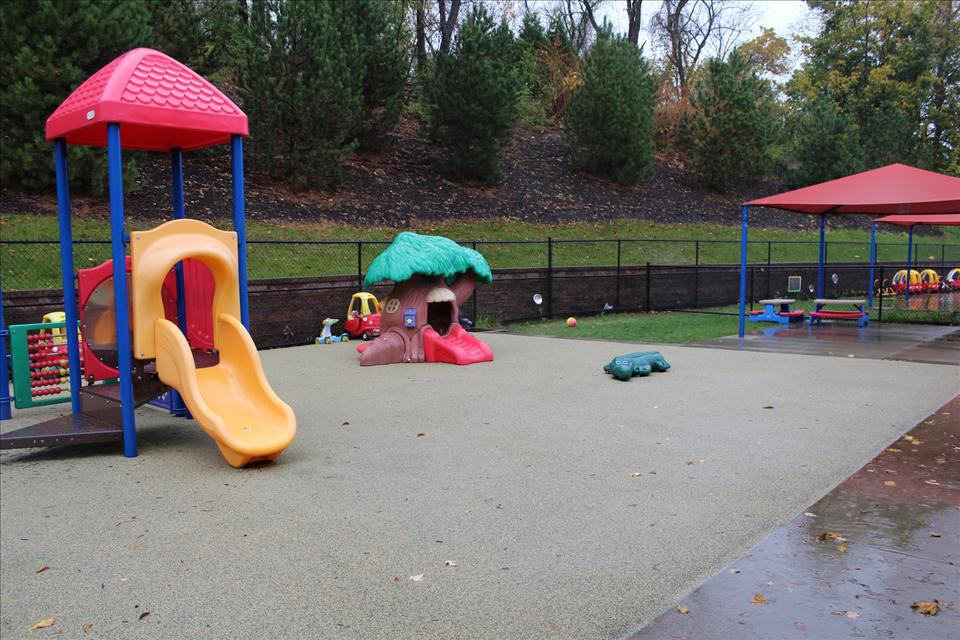 This is our Infant, Toddler, and Discovery Preschool playground. Our smaller students love riding cars, exploring the tree house, and playing on the outdoor piano.