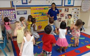 "Ms. Leela encouraging gross-motor skills with preschool students by dancing to the ""Hokie Pokie""!"