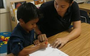 4 year old Jaekob is working with Ms. Samantha on his colors in his Spanish journal.