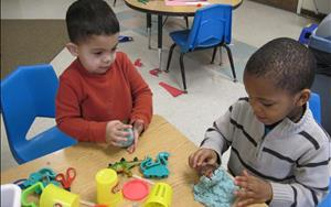 These children are exploring and creating with dinosarus & play-dough during center/area time in the preschool classroom.