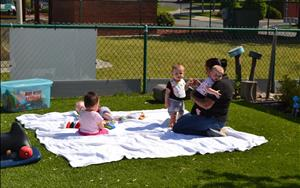 Some of the infants enjoying outside time with Ms. Sashi.