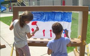 Our school-age children develop fine motor skills and explore their creativity while painting on the playground