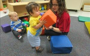 Ms. Anna enjoys building towers with the children to strengthen their fine-motor skills.