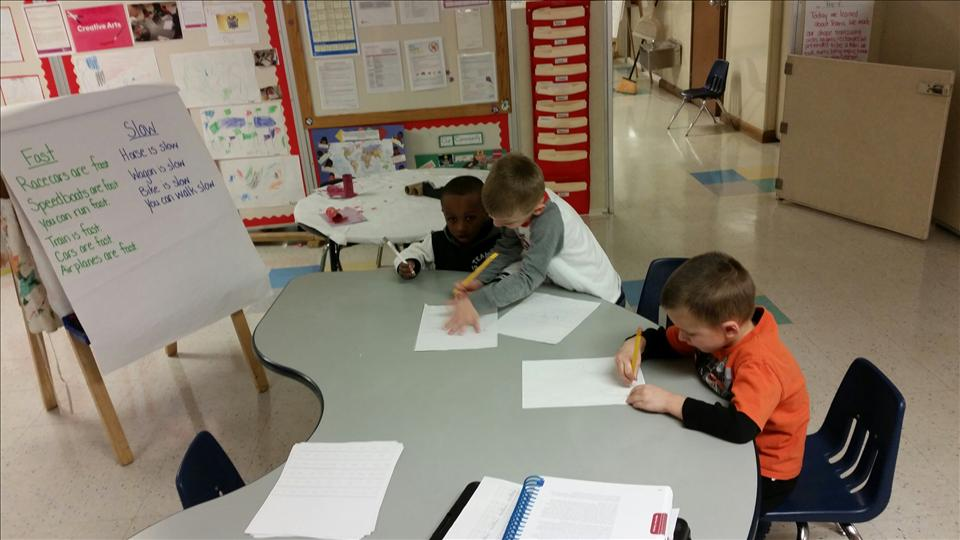 Chase, Keagan and Marcus writing sentences using the chart that was created.