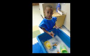 A preschooler enjoys sensory fun in the water table.