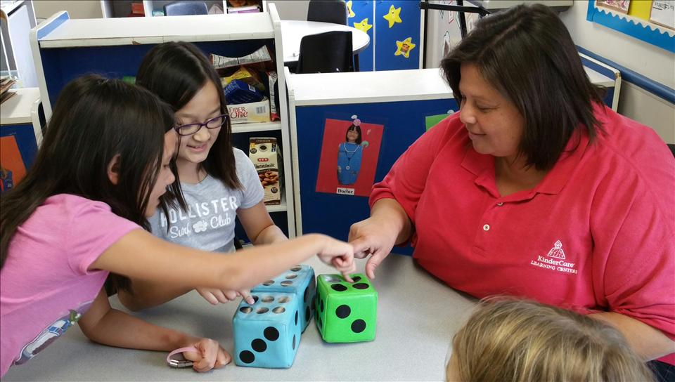 Excellence in Education award winner Ms. Ruby working with school-age children on a math game.