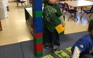 A toddler building blocks as high as he can