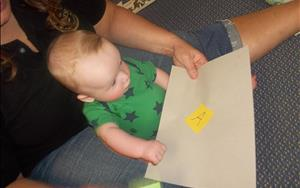 Infant is being exposed to literacy.