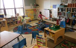Children are exploring various areas during center time, such as Art and Dramatic Play in the Preschool classroom.