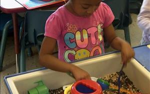 Playing in the sensory table in Pre-Kindergarten.