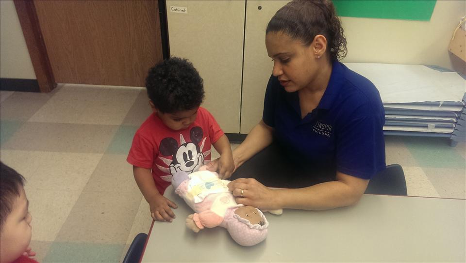 Ms. Carmen playing with a baby with the children.