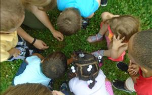PreSchool and Pre K Students with a Naturalist learning about what is on/in the ground.
