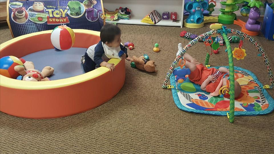 Two children exploring and playing with toys in our Infant Classroom.