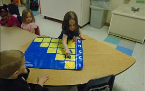 Hailey counting shapes using the counting mat.