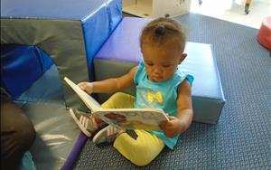 Literacy is important at every age! Skye likes to look at books in our nursery.
