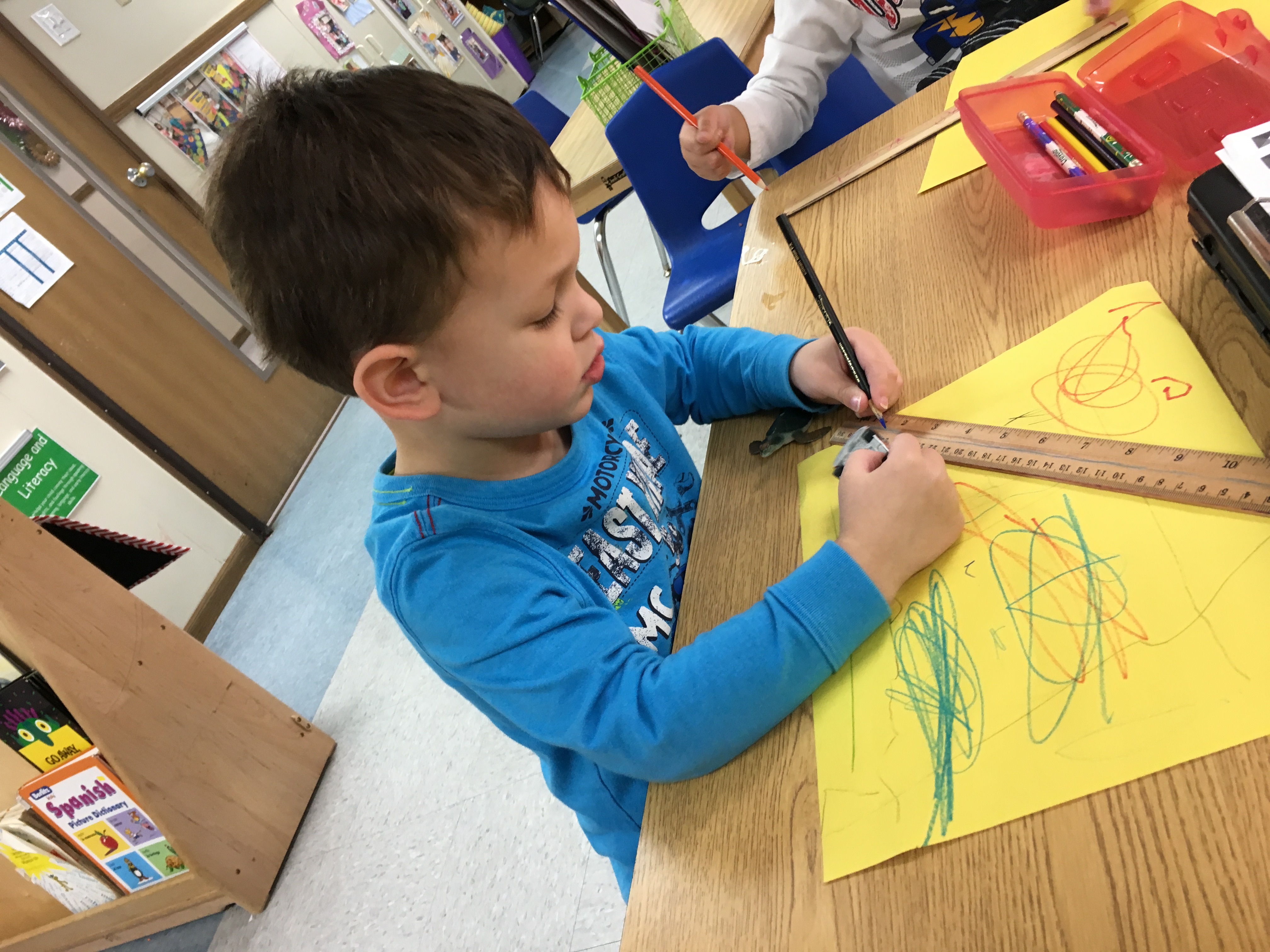 Practicing writing and measuring skills in the Preschool Classroom.